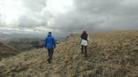 Een groep toeristen drie mensen loopt hoog in bewolkt weer op de rand van het plateau in de bergen Langzame Motie stock footage