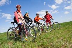 Een groep van vier volwassenen op fietsen. Royalty-vrije Stock Foto's