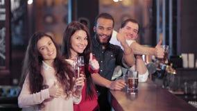 Een groep vrienden bij de bar met bier het glimlachen stock videobeelden