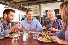 Een groep vrienden die bij een restaurant eten Royalty-vrije Stock Afbeeldingen