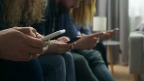 Een groep vrienden gebruikt smartphones in de woonkamer stock footage