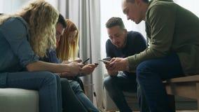 Een groep vrienden gebruikt smartphones in de woonkamer stock video