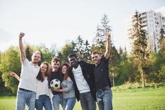 Een groep vrienden in het toevallige voetbal van het uitrustingsspel in openlucht De mensen hebben pret en hebben pret Actieve ru royalty-vrije stock afbeelding