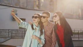Een groep vrienden maakt selfie, maken zij een grappig gezicht De rode stralen van de zon op een achtergrond van een oud gebouw stock video
