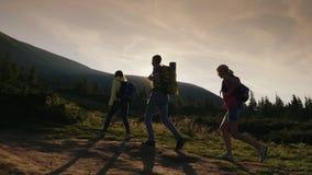 Een groep vrienden met rugzakken neemt op de berg toe In de stralen van de het plaatsen zon Actieve levensstijl stock video