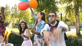 Een groep vrienden in partijhoed en partijhoorn die pret hebben en de verjaardag vieren stock footage