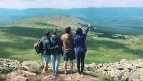 Een groep vrienden, toeristen die bovenop de berg rusten stock videobeelden
