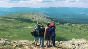 Een groep vrienden, toeristen die bovenop de berg rusten stock video