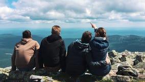 Een groep vrienden, toeristen die bovenop de berg rusten stock footage
