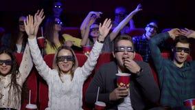 Een groep vrolijke vrienden let op 3D film in glazen in de bioskoop stock video
