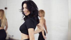 Een groep vrouwelijke dansers die bachata hoofdelementen leren Verdraaiend lichaam en schuddend hoofd Hip bewegingen van Latijnse stock footage