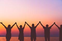 Een groep vrouwen neemt handen tot het concept van de hemelvrijheid met blauwe hemel en strandzonsondergang toe royalty-vrije stock afbeelding