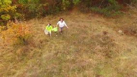 Een groeps mensen looppas uit het de herfstbos stock videobeelden