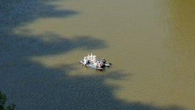Een groeps mensen vlotten langs de rivier stock footage