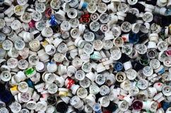 Een groot aantal kappen van blikken van aërosolverf voor graffiti Gesmeerd met gekleurde verf liggen de pijpen in een reusachtige royalty-vrije stock foto's