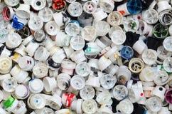 Een groot aantal kappen van blikken van aërosolverf voor graffiti Gesmeerd met gekleurde verf liggen de pijpen in een reusachtige stock foto