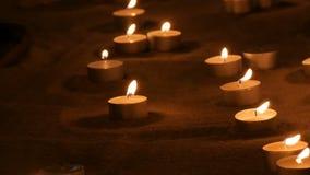 Een groot aantal kleine witte ronde kaarsen die in het zand branden Achtergrond van het branden van kaarsen stock footage