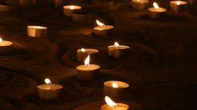 Een groot aantal kleine witte ronde kaarsen die in het zand branden Achtergrond van het branden van kaarsen stock video