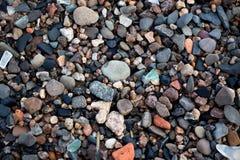 Een groot aantal kleurrijke en diverse stenen op de kust van het meer Stock Foto