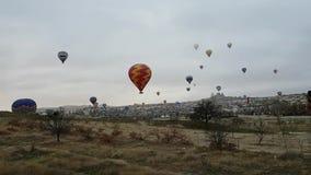 Een groot aantal kleurrijke heldere ballons vliegt in de ochtendnevel over Cappadocia Dawn en wolken over Goreme Langzame Vlucht stock footage