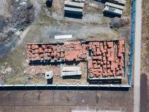 Een groot aantal rode bakstenen die op pallets dichtbij de bouwwerf in openlucht worden gestapeld, ingesloten door een omheining, royalty-vrije stock foto