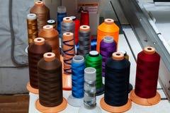 Een groot aantal spoelen met gekleurde draden in een workshop voor het naaien van en het vervoeren van textiel voor de automobiel stock fotografie