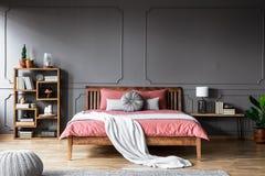 Een groot bed in een ruime, donkere slaapkamer die zich tussen een plank bevinden stock foto
