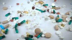 Een groot en gevarieerd assortiment van farmaceutische drugs of vitaminesupplementen valt binnen tegen een witte achtergrond stock videobeelden