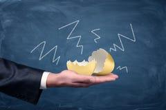 Een groot gebarsten en leeg gouden ei die op een zakenman` s palm liggen met negatieve die pijlen op een bord rond het worden get royalty-vrije stock foto