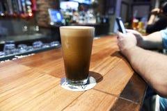 Een groot lang glas schuimend heerlijk bier bij een bar stock foto's