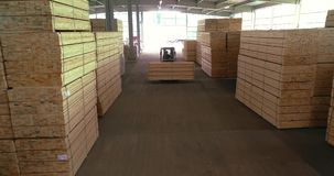 Een groot pakhuis van houtmaterialen Een vorkheftruck draagt een houten straal door het pakhuis Keurig gestapelde houten bar stock video