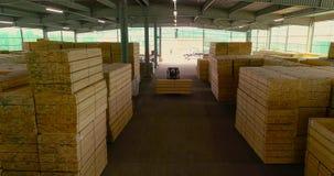 Een groot pakhuis van houtmaterialen Een vorkheftruck draagt een houten straal door het pakhuis Keurig gestapelde houten bar stock videobeelden