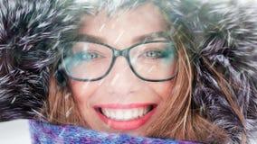 Een groot portret van een meisje die glazen in een bontkap dragen in de winter stock videobeelden