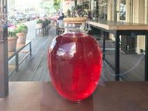 Een groot rood transparant glas om lichtgevende helder kan met een houten deksel, een container met heerlijk zoet sap, belemmer,  stock foto's