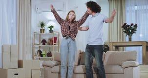 In een groot ruim woonkamer charismatisch paar die een grote bank in de woonkamer dragen die van de tijd in nieuw genieten stock footage
