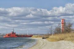 Een groot vrachtschip gaat dichtbij de vuurtoren over tot de haven van een containerterminal in de Mykolaiv-zeehaven stock afbeeldingen