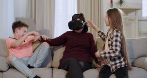 Een grootmoeder die de virtuele wereld onderzoeken die een VR gebruiken voor het eerst, zij zitting op de bank met haar kleinkind stock video