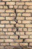 Een grote barst in de oude steenmuur Achtergrond van een steenbakstenen muur van een gebouw met diep door gevaarlijke barst geruï stock foto