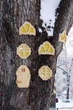 Een grote boomstam van snow-covered hout waarop van triplex ronde, gesneden Vensters en deuren voor kinderen om worden gemaakt te stock foto