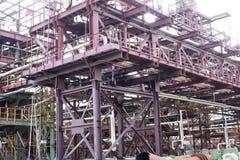 Een grote de leidingenschraag van het ijzermetaal met pijpen en elektrische draden en materiaal bij de petrochemische raffinaderi royalty-vrije stock fotografie
