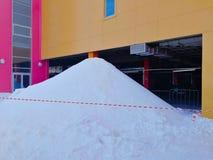 Een grote die stapel van sneeuw, met een speciaal rood en wit gestippeld die lint wordt geschermd, door het dak wordt gevormd sch royalty-vrije stock foto