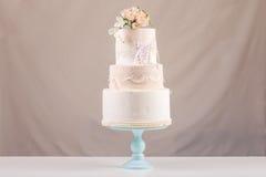 Een grote die tiered huwelijkscake in de vorm van kleding met kant met roze rozen bovenop de lijst wordt verfraaid Royalty-vrije Stock Fotografie