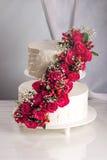 Een grote die tiered huwelijkscake met rode rozen op de lijst wordt verfraaid Stock Afbeelding
