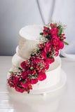 Een grote die tiered huwelijkscake met rode rozen op de lijst wordt verfraaid Royalty-vrije Stock Afbeelding