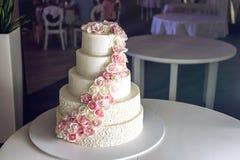 Een grote die tiered huwelijkscake met roze rozen op de lijst in het restaurant wordt verfraaid Stock Afbeelding