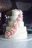 Een grote die tiered huwelijkscake met roze rozen op de lijst in het restaurant wordt verfraaid Royalty-vrije Stock Afbeeldingen