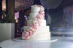 Een grote die tiered huwelijkscake met roze rozen op de lijst in het restaurant wordt verfraaid Royalty-vrije Stock Foto's