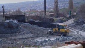 Een grote gele bulldozer harkt de klei dichtbij de installatie stock videobeelden