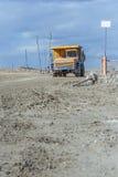 Een grote gele stortplaatsvrachtwagen die in een steengroeve werken Royalty-vrije Stock Afbeelding