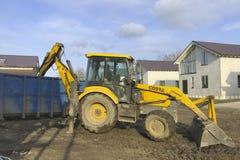 Een grote gele tractor laadt bouwhuisvuil in een container met een emmer royalty-vrije stock foto's